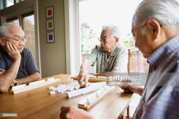 Three elderly men sitting at table playing game