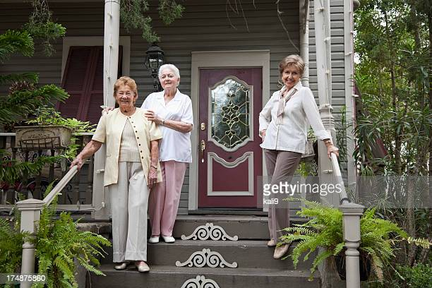 Three elderly women in front of house