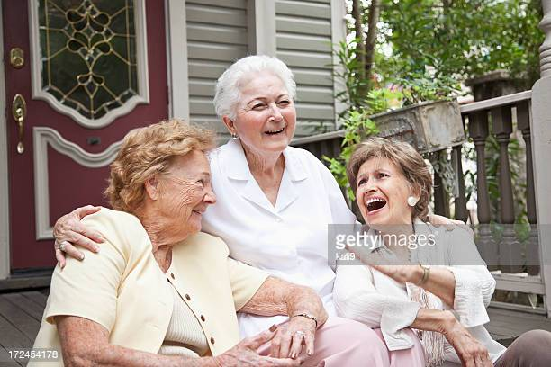 Three elderly women sitting in front of home