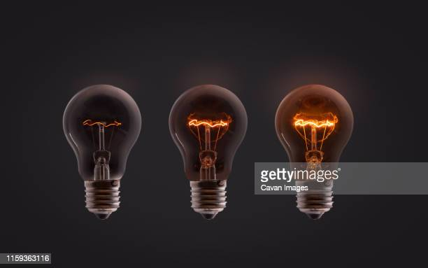 three electric bulbs powered at different electrical intensities - persuasion stock pictures, royalty-free photos & images