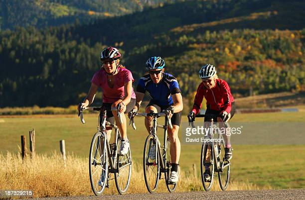 Three elite cyclists on country road in fall