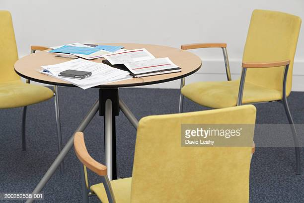 Three empty chairs around meeting room table covered in documents