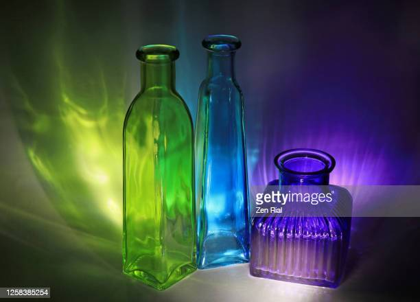 three empty colored bottles casting colored shadows in the dark - translucide photos et images de collection