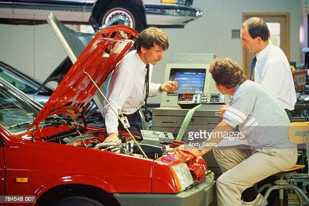Three engineers in auto laboratory testing performance of car engine