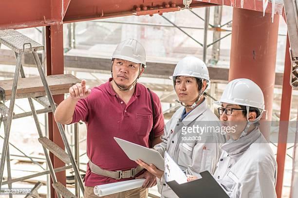 3 つのエンジニアの点検、ビルディング建設現場