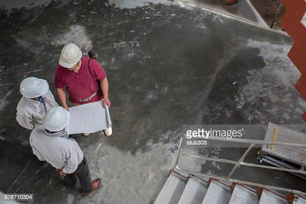 Three engineers looking at some papers at building site