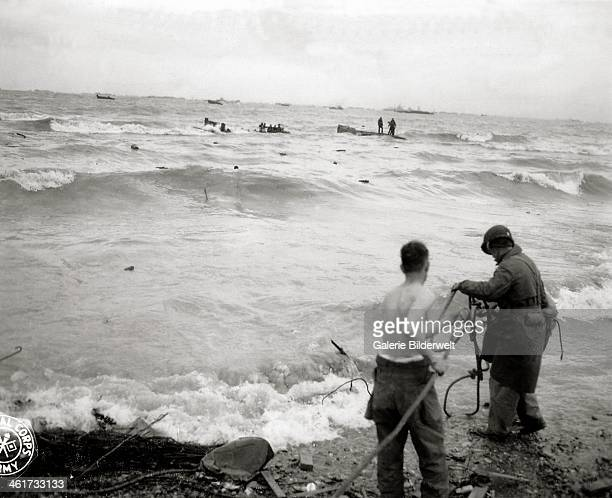 Three Engineers prepare a rope to support a shipwrecked soldier near Omaha Beach 6th June 1944 In the background is the cruiser USS Augusta flagship...