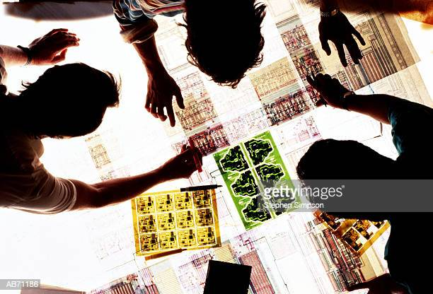 three engineers viewing technical drawings on lightbox, overhead view - lightbox stock pictures, royalty-free photos & images