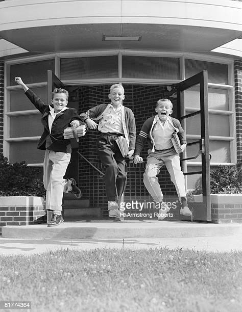 three excited boys running out of school. (photo by h. armstrong roberts/retrofile/getty images) - bambini scuola bianco e nero foto e immagini stock