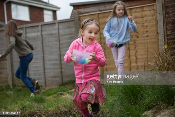 three excited children on an easter egg hunt in a back yard - easter egg hunt stock pictures, royalty-free photos & images