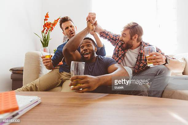 three excited guys watching sport on tv - match sport stock pictures, royalty-free photos & images