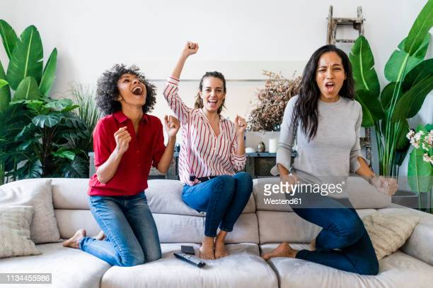 three excited women on couch at home watching tv and cheering - guardare con attenzione foto e immagini stock