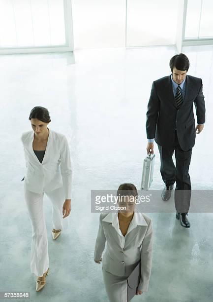 Three executives entering office building lobby