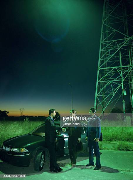 Three executives meeting beside car in remote location, night