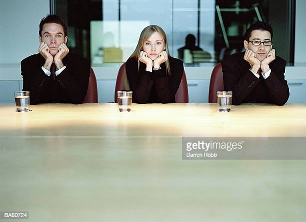 Three executives resting heads in hands