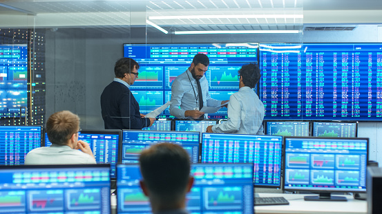 Three Experienced Stock Traders Talking Business, Consulting Documents and Argue About Data. They Work for a Big Stock Exchange Firm. Office is Full of Displays Showing Infographics and Numbers. 866662328