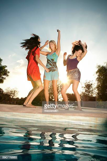 Three exuberant young women having a party at the poolside