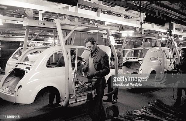 Three factory workers of FIAT are at work They assemble the bodywork of a FIAT Cinquecento Turin Italy 1964