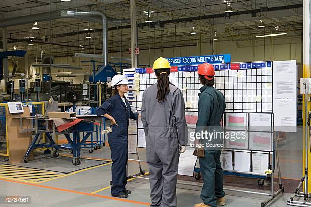 Three factory workers standing near message board