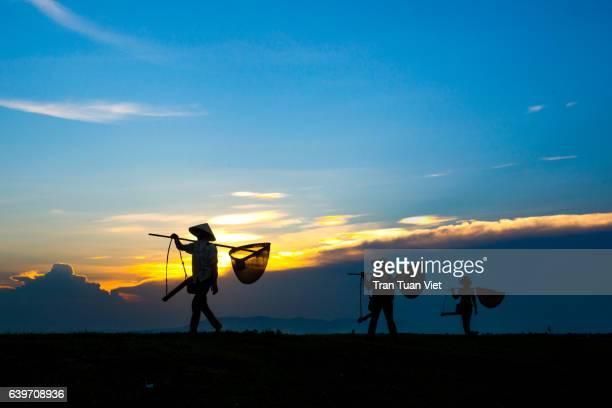 three farmers in twilight - ナムディン ストックフォトと画像