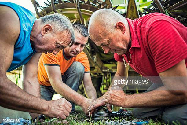 Three farmers repairing combine harvester parts