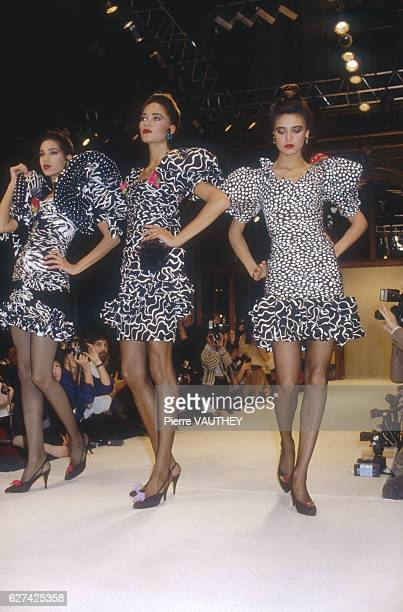 Three fashion models wear haute couture blackandwhite cocktail dresses by French fashion designer Emanuel Ungaro They are modeling the dresses during...