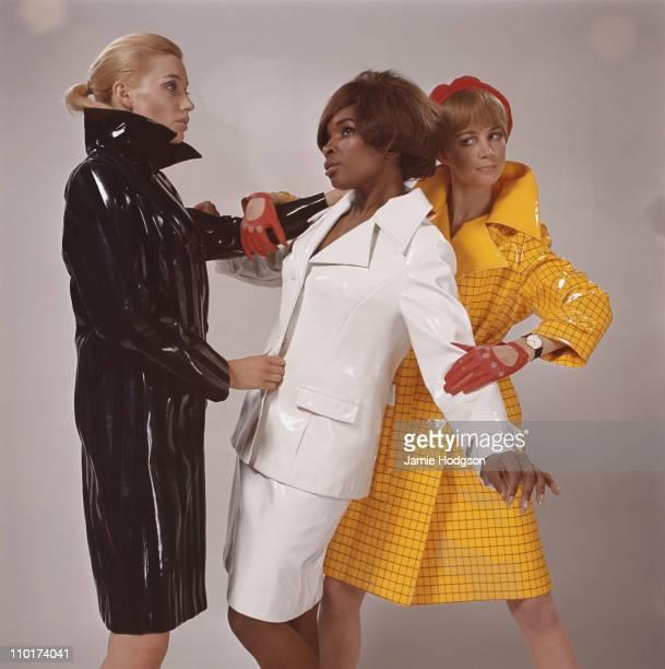 Three fashion models wearing waterproof clothing circa 1965