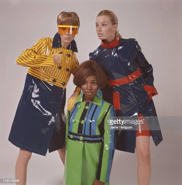 Three fashion models wearing waterproof coats circa 1965