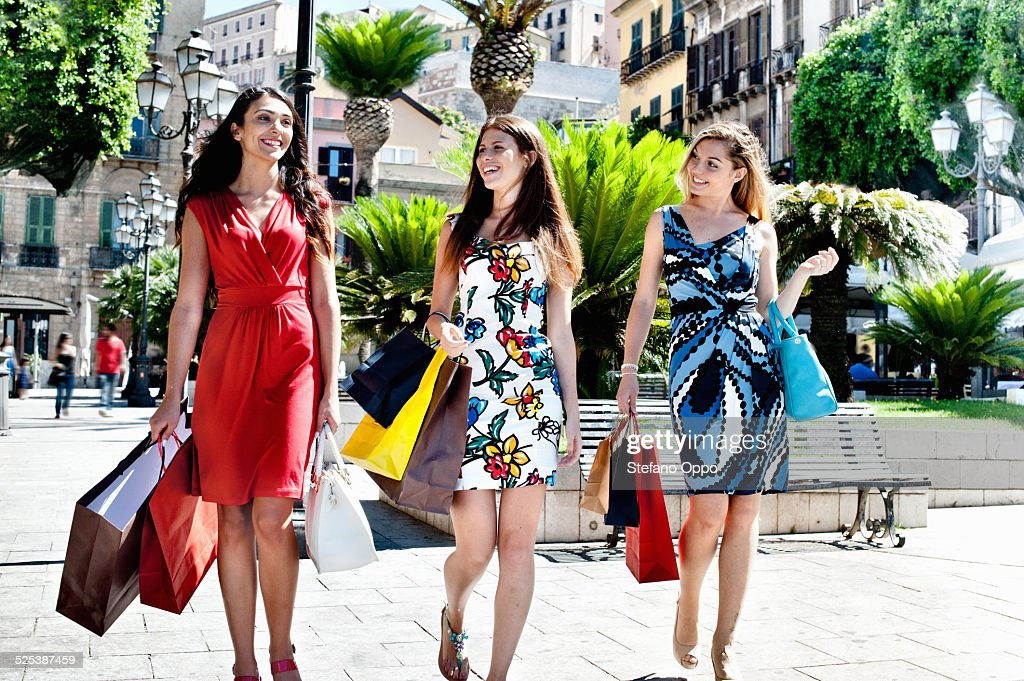 Three fashionable young women strolling with shopping bags, Cagliari, Sardinia, Italy : Stock Photo