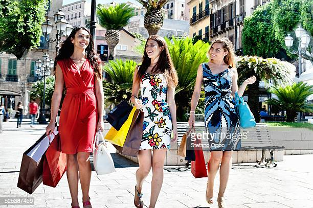 Three fashionable young women strolling with shopping bags, Cagliari, Sardinia, Italy