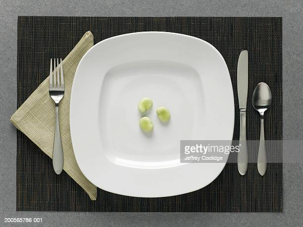 three fava beans on plate with table setting, elevated view - small group of objects stock pictures, royalty-free photos & images