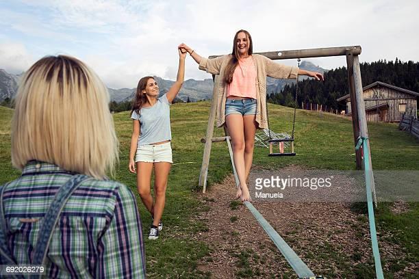 Three female adult friends balancing on slackline in Austrian Alps, Sattelbergalm, Tirol, Austria
