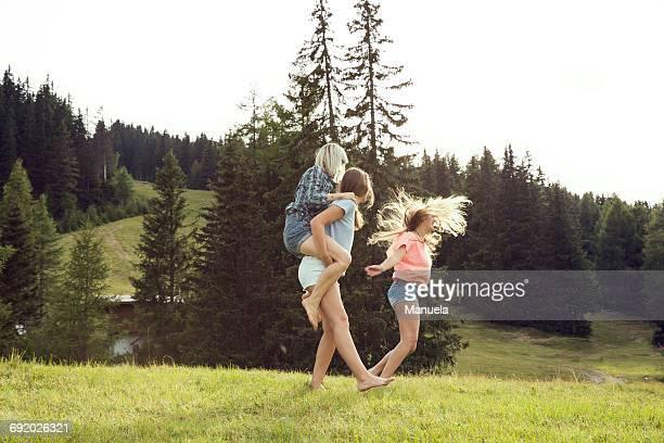 Three female adult friends piggyback racing in field, Sattelbergalm, Tirol, Austria