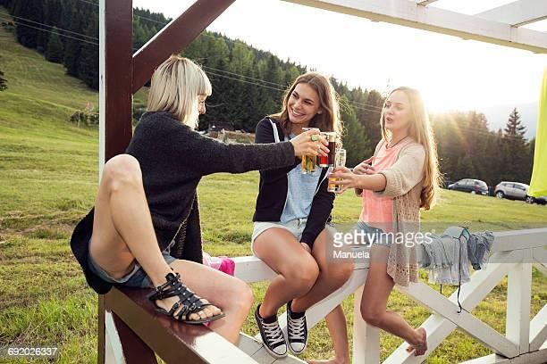 Three female adult friends raising a glass on porch, Sattelbergalm, Tirol, Austria