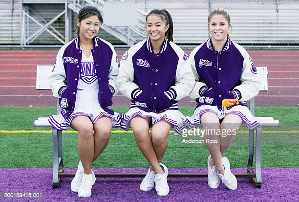 three female cheerleaders (16-18) sitting on bench, smiling, portrait - asian cheerleaders stock photos and pictures