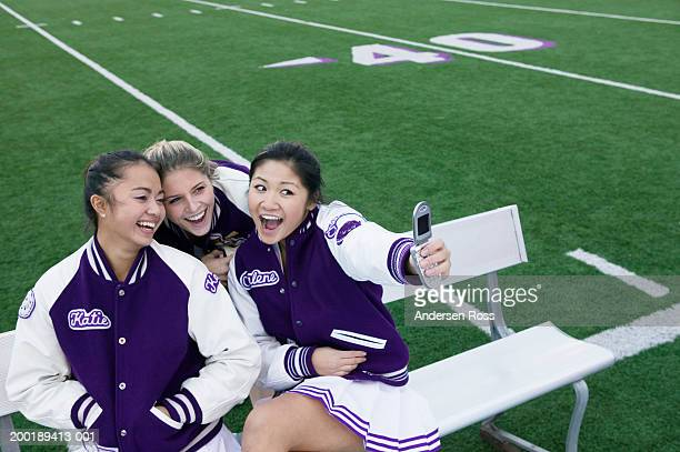 three female cheerleaders (16-18) taking photograph with camera phone - asian cheerleaders stock photos and pictures