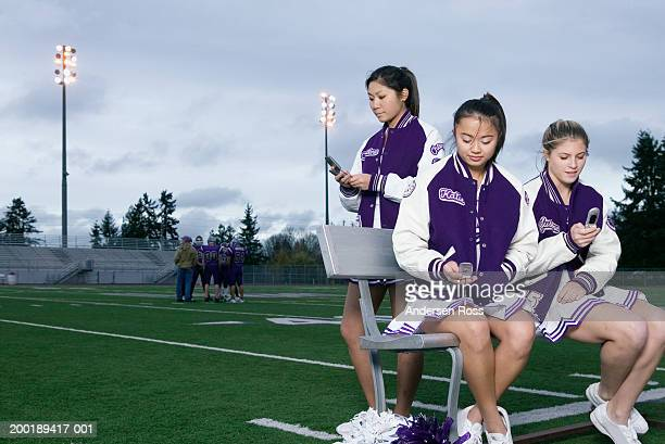 three female cheerleaders (16-18) using cell phones beside field - asian cheerleaders stock photos and pictures