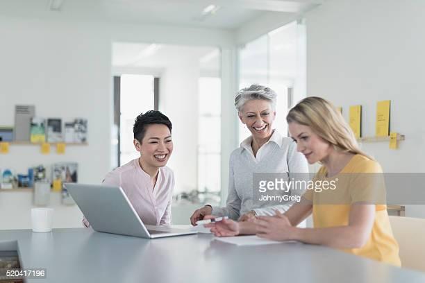 Drei weibliche Kollegen lächelnd in Treffen mit Laptop