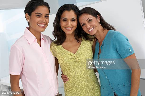 Three female colleagues standing together, smiling, portrait