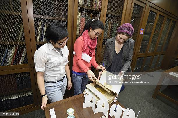 Three female college students are beginning to look through a binder at a library event February 11 2016