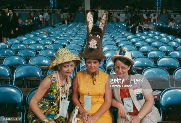 Three female Democratic Party members wearing distinct hats two wear different styles of straw hat and the third wears hat in the shape of a donkey...