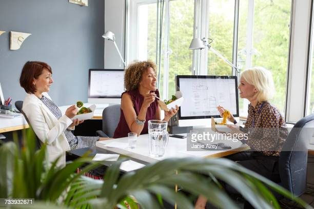 Three female designers having working lunch meeting in office