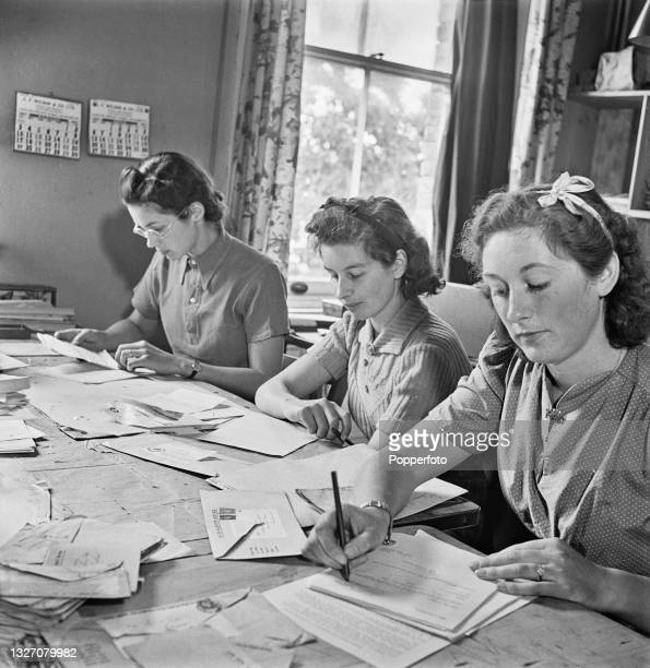 Three female employees from the Army Record Office, a department of the British Army that deals with military service records, write sympathetic...