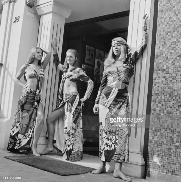 Three female fashion model wearing printed dresses, UK, 24th October 1969.