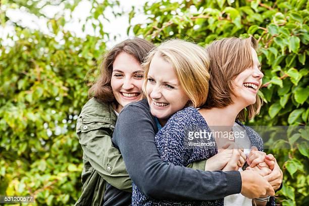 Three female friends hugging in garden