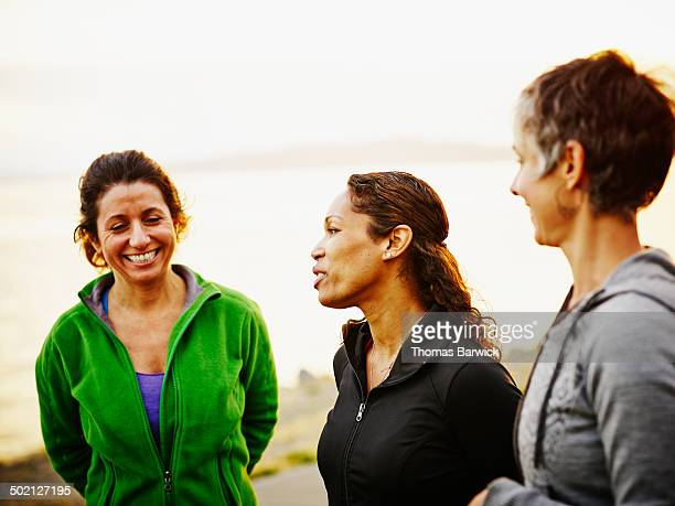 Three female friends laughing together after run