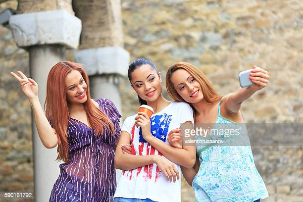 Three female friends making selfie outdoors