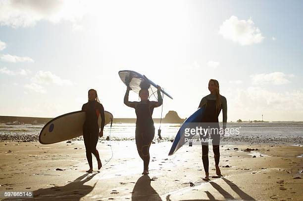 Three female friends on beach, holding surfboards