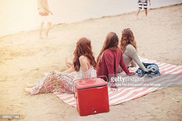 Three female friends sitting on picnic blanket on beach
