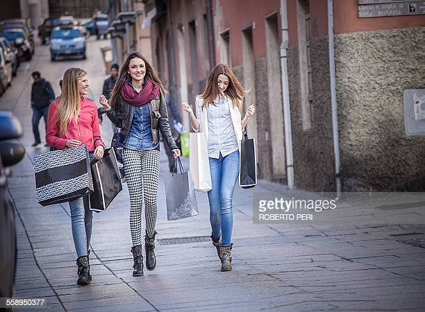 Three female friends strolling along street with shopping bags, Cagliari, Sardinia, Italy